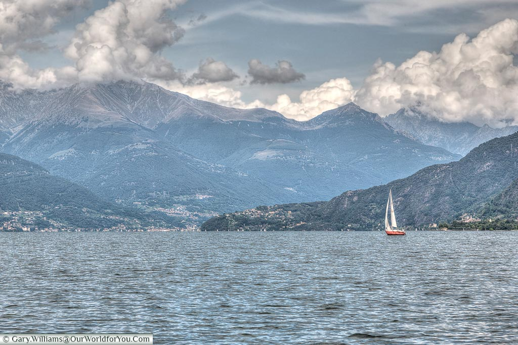 A small sail boat on the Lake Como dwarfed by the mountains the surround the north of the lake.