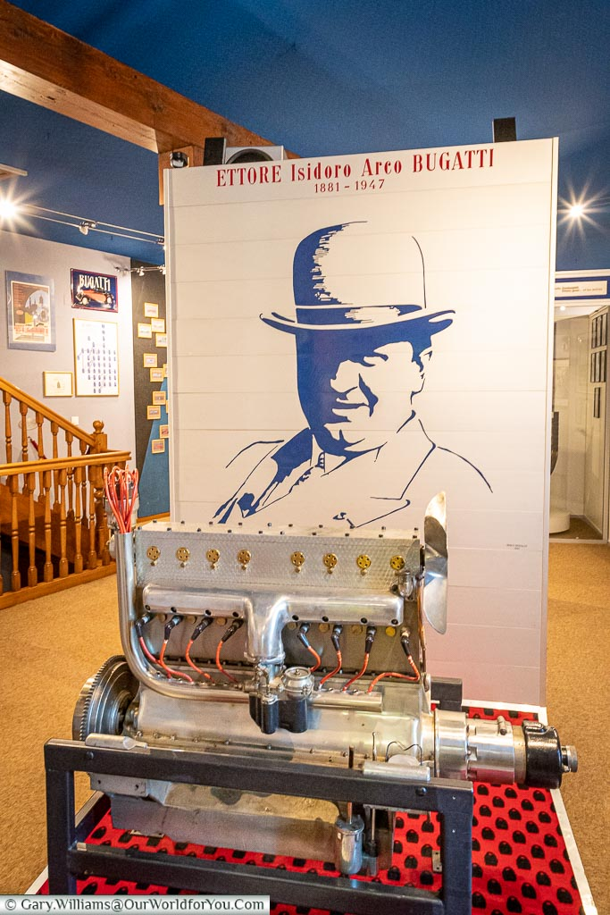 A display inside the Bugatti museum of a type 45 engine infron of an image of Ettore Bugatti.