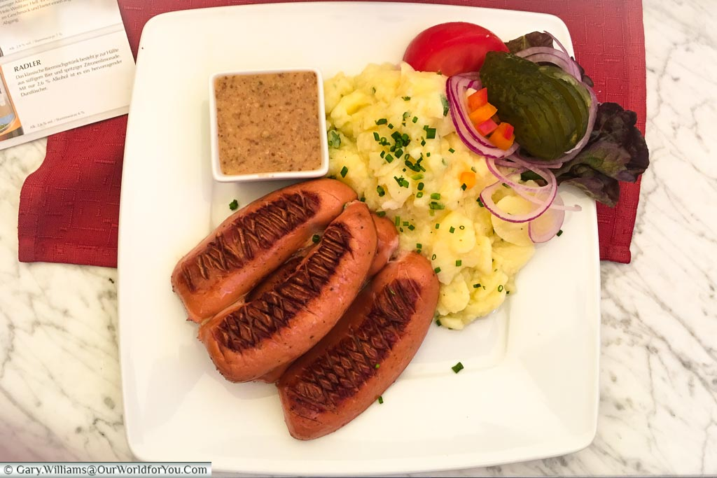 A plate of grilled Regensburger sausages served with potato salad pickles, and mustard from the Ratskeller, Regensburg.