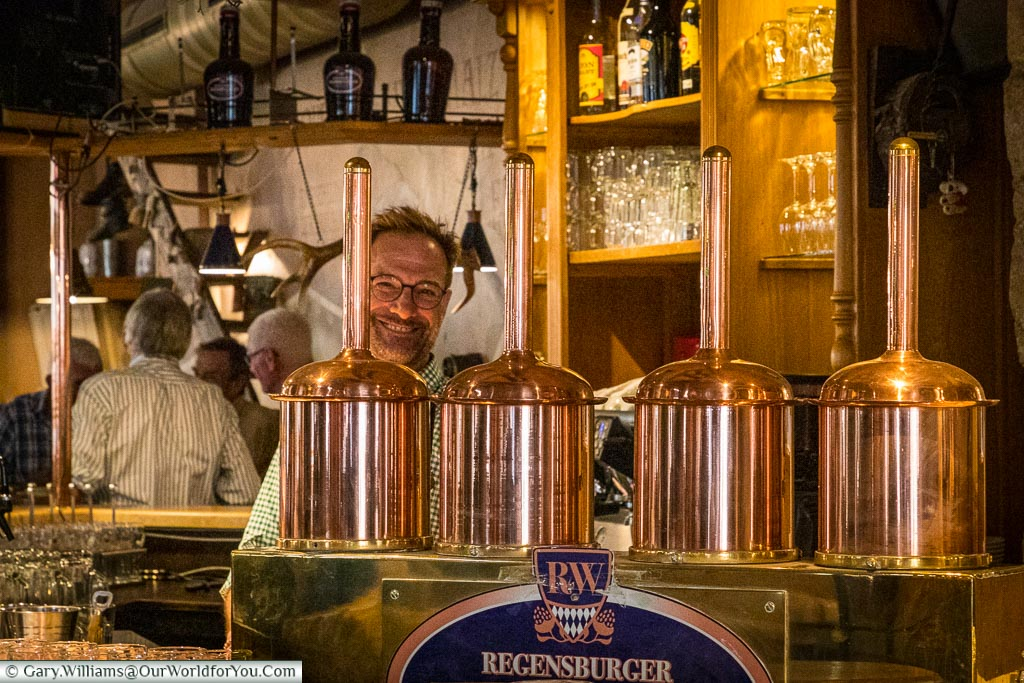 The view of the bar inside the Regensburger Weissbräuhaus, Regensburg, dominated by polished copper pumps and a friendly, smiling, barman.