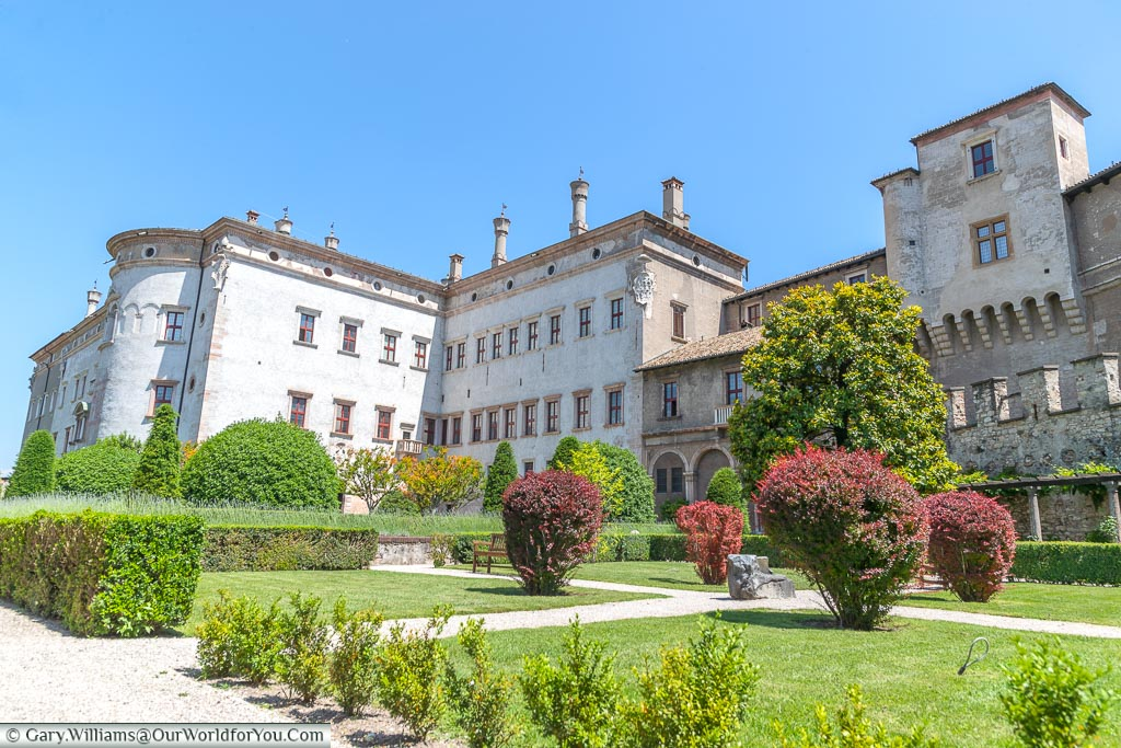 The gardens of the Buonconsiglio Castle Museum looking back of the white stone castle on a bright sunny day with clear blue skies.