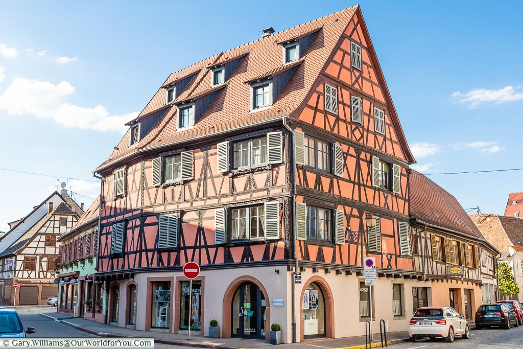 A half-timber building, typical of Alsatian architecture painted in a dusky orange colour.
