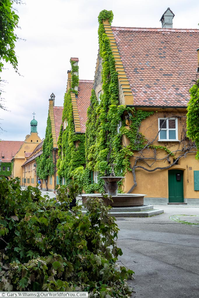 A view of the cast-iron fountain in front of the rows of terraces of the Fuggerei.