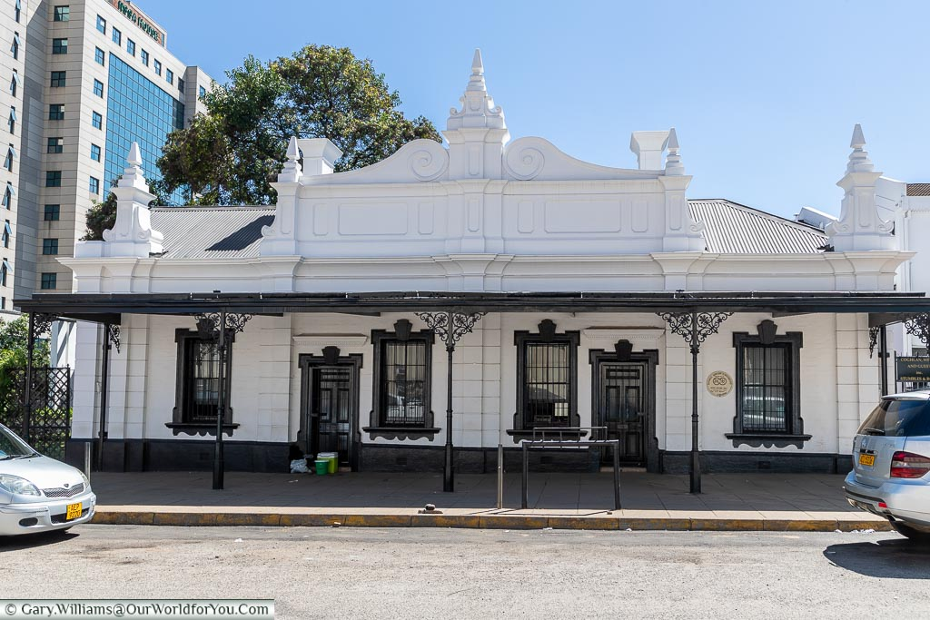 A white stone, Colonial-era, building with black trimmings and wrought iron guttering,