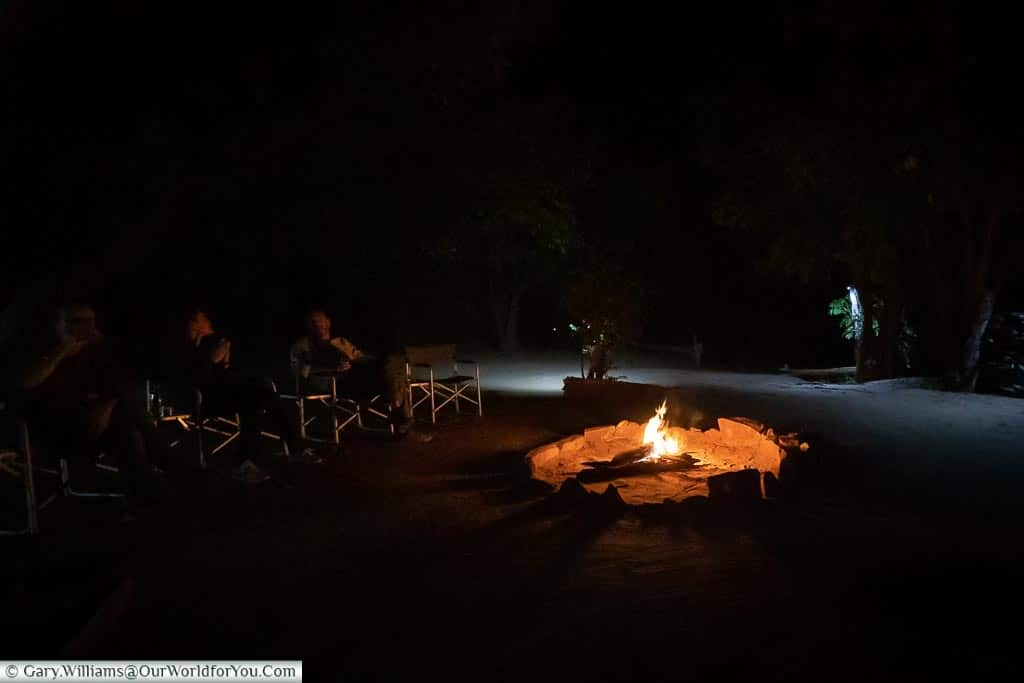 A small group sitting around an open-air fire pit, with a roaring fire.
