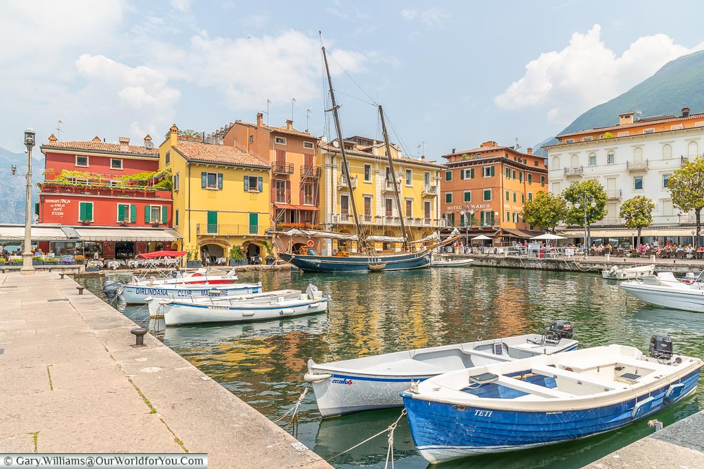 The quaint old harbour of Malcesine lined on two sides with colourful buildings.  In the port, there are several small boats and one larger rigged sailboat.