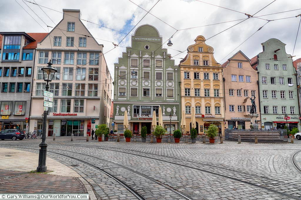 A row of historic buildings at a junction on Maximilianstraße each on in a different period colour.