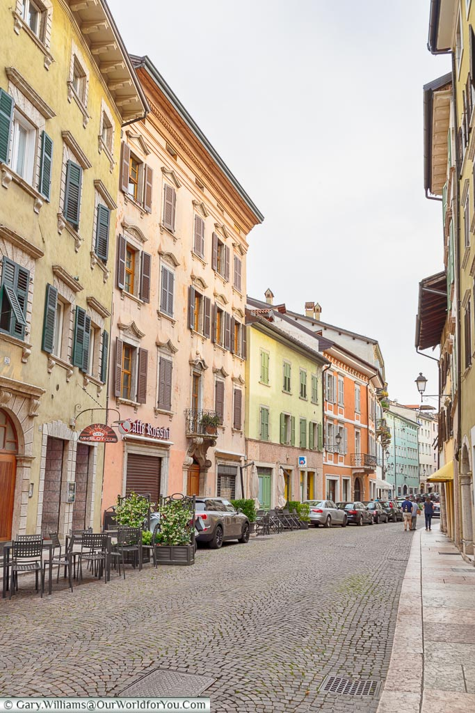 A street scene of Trento with pastel coloured four-storey buildings.