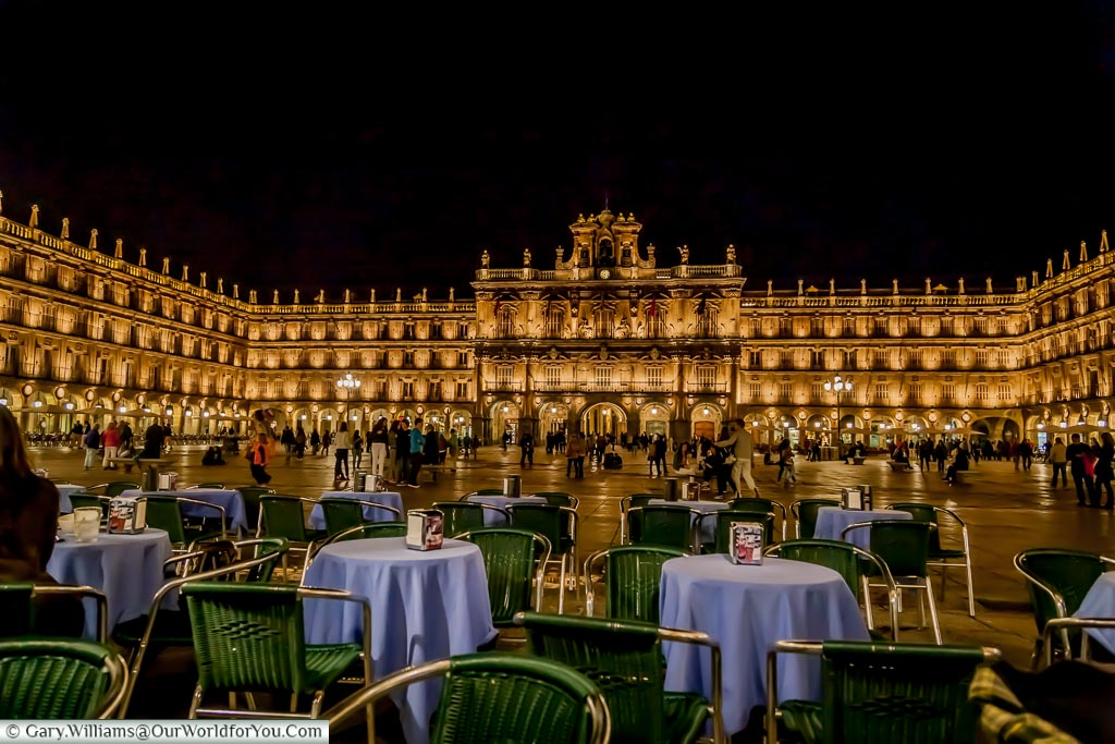 The view Plaza Mayor in Salamanca, illuminated at night, from a table of a bar.