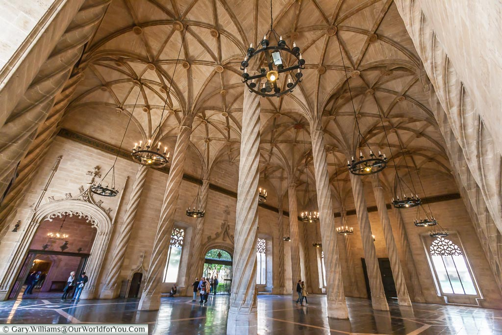 Inside the Silk Exchange of Valencia with its high vaulted roof and spiral columns.
