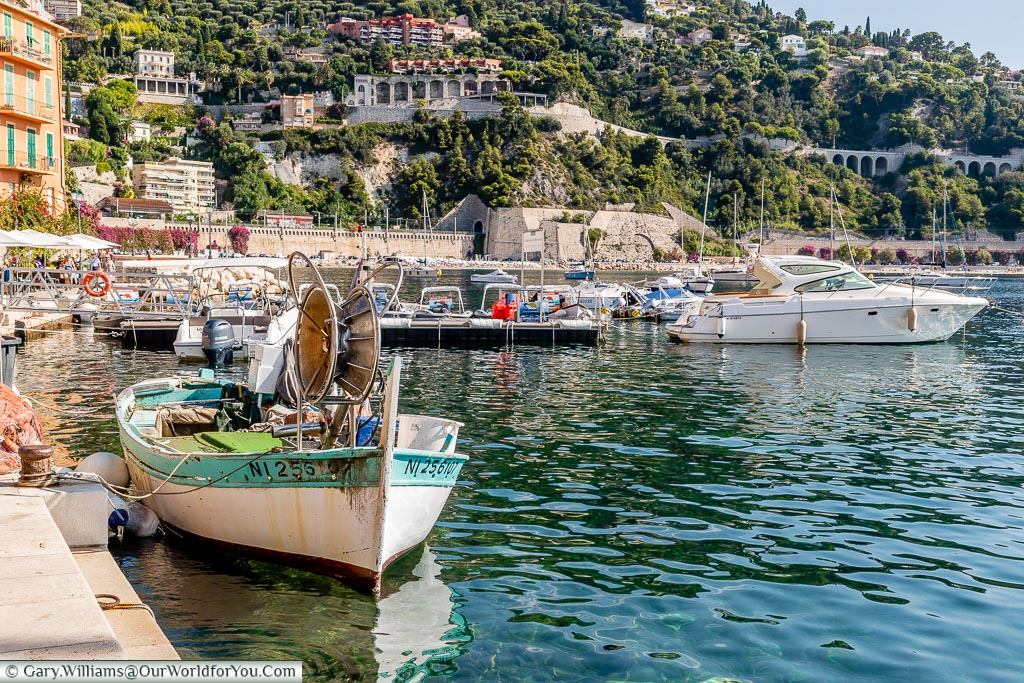 The harbour of Villefranche-sur-Mer, with a small fishing boat in the foreground and the hillside in the background.