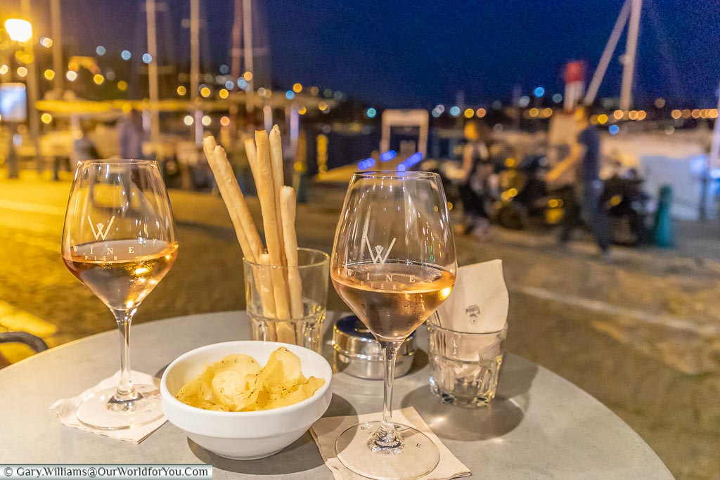 Two glasses of rosé wine in front of the harbour of Villefranche-sur-Mer at night.