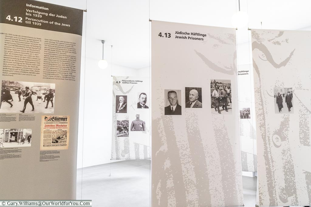 Inside a corner of a museum where drapes display information of the horrors of the camps with supporting images.
