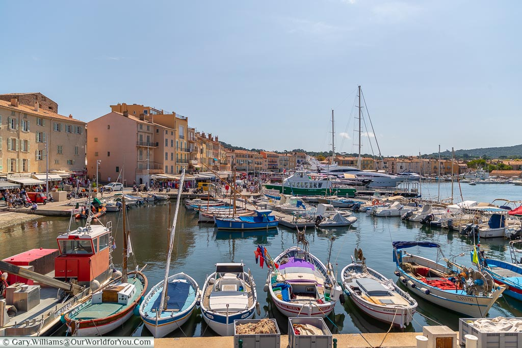 Looking down on the old harbour of Saint Tropez from the raised city walls.  The old port is filled with traditional, small, fishing boats, but in the background, you can also make out the super yachts this town is famous for.