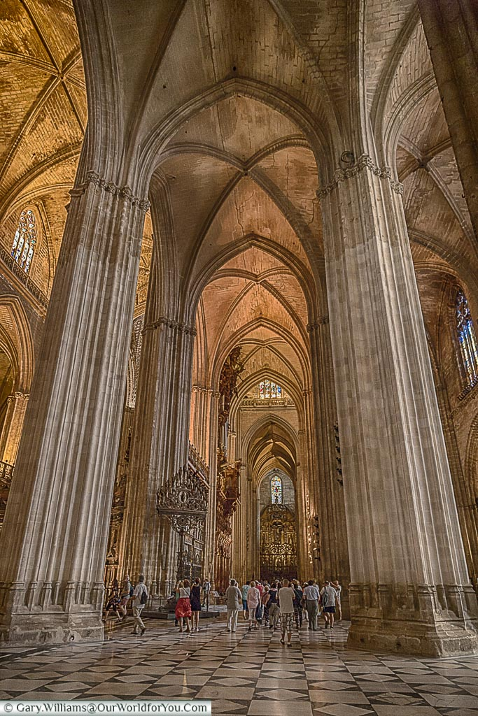 A portrait view inside Seville's gothic cathedral with a group at the base of one of its vast columns that support its substantial vaulted ceiling.