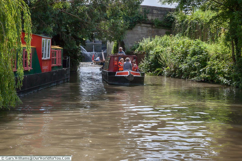 A narrow beam canal boat is exiting a lock with the children wearing life vests as a safety precaution.