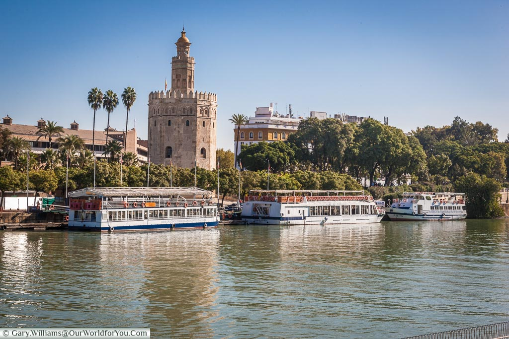 Tourist pleasure boats line the edges of the Guadalquivir river in front of the Moorish Torre del Oro.