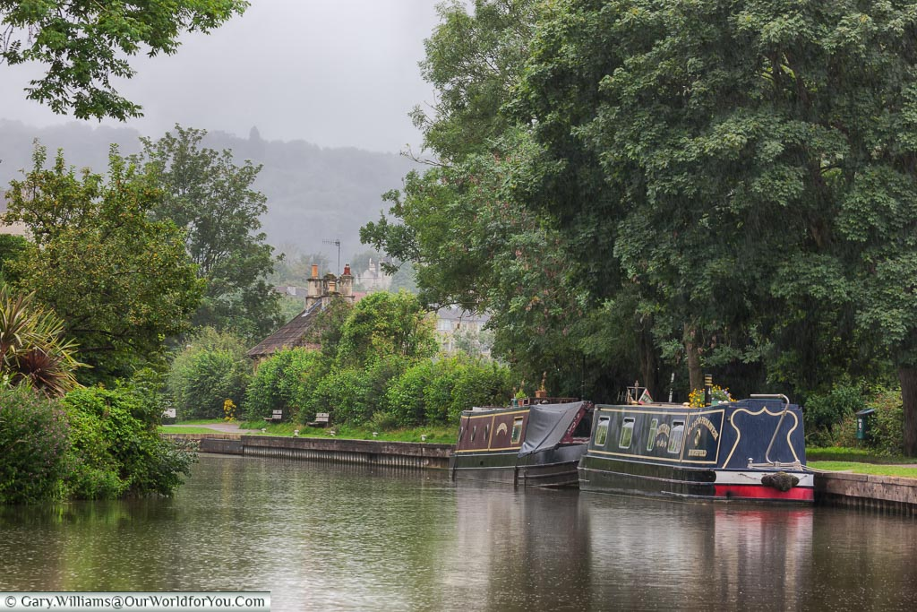 Narrowboats moored up alongside a towpath as the rain sets in.  One of the perils of barging in the UK, even in summer.