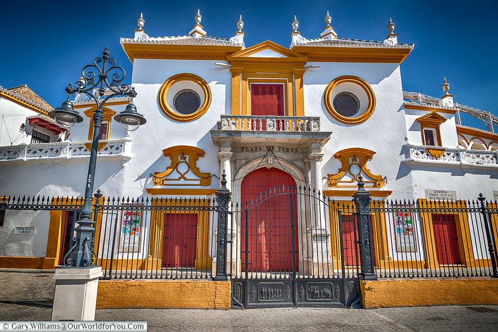 The traditional main entrance to Plaza de Toros, or bullring.  The doors are painted a deep red against a white building with Ocre coloured details.