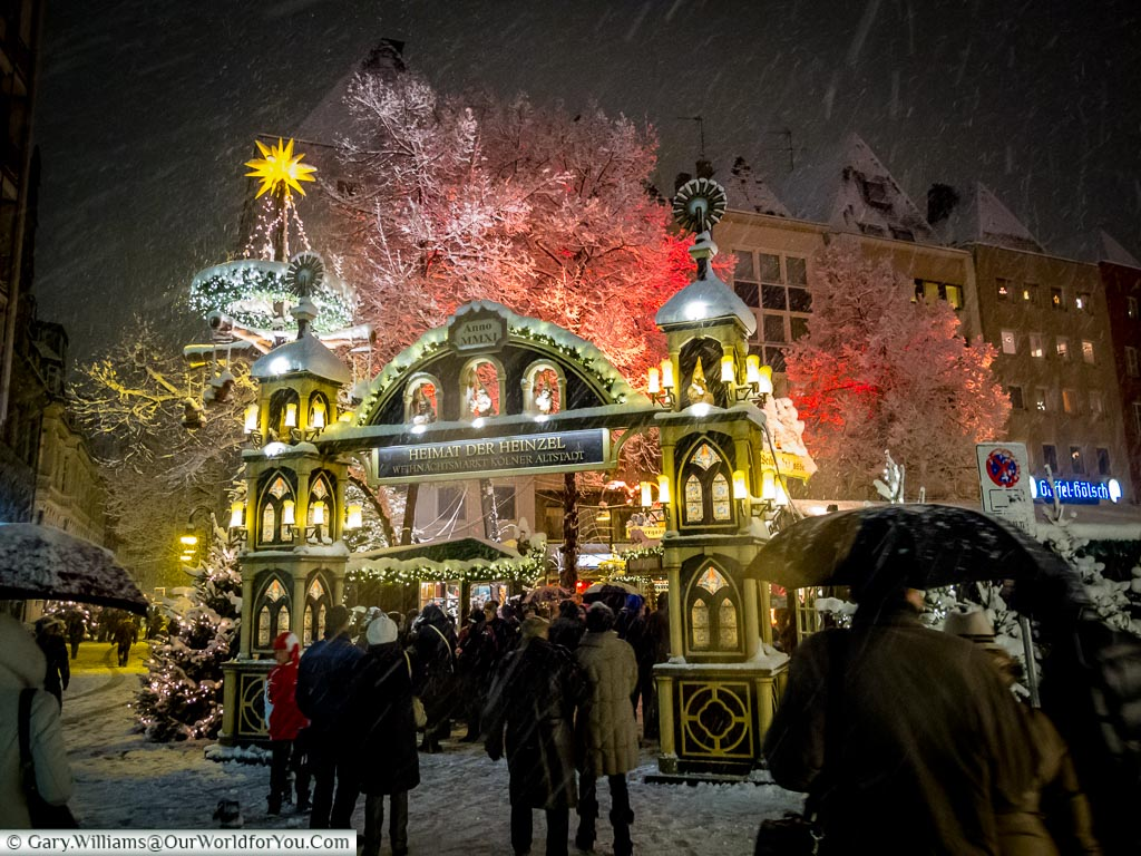 People entering through an advent arch into the Meimat der Heinzel market as snow falls in an already wintery scene.
