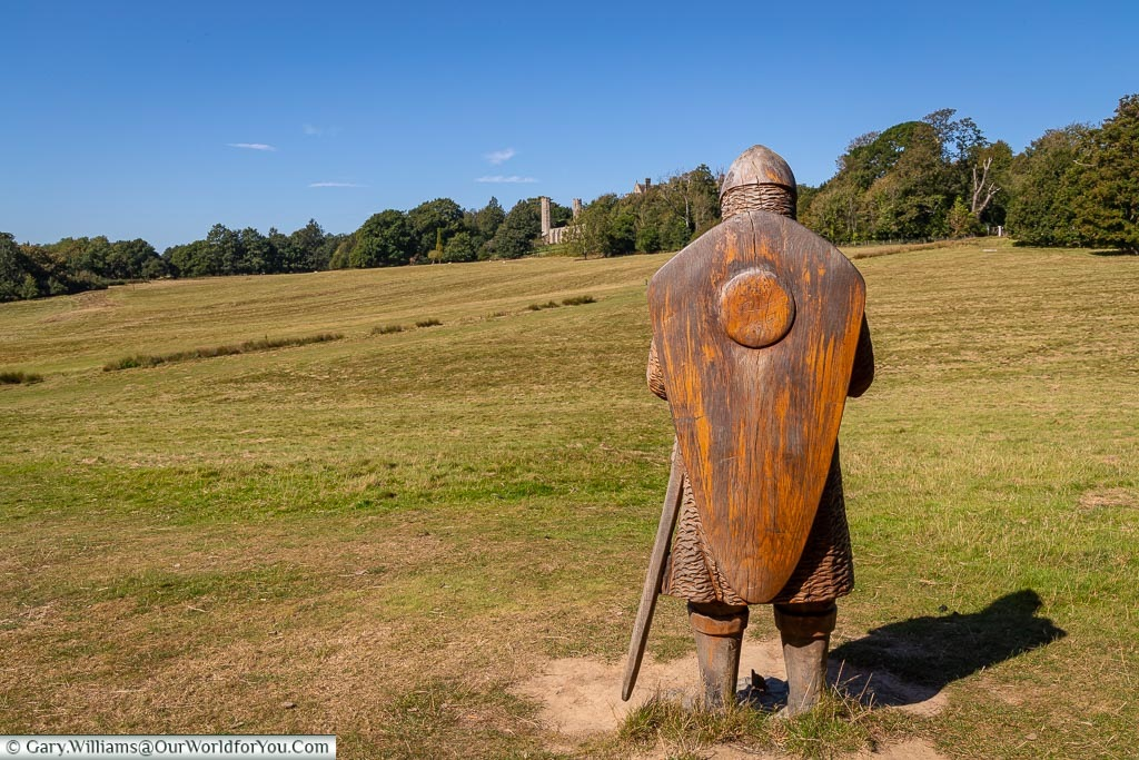 The view of the back of a carved wooden statue of a Norman Soldier overlooking the green rolling landscape of the battlefield at Battle with the Abby in the distance.