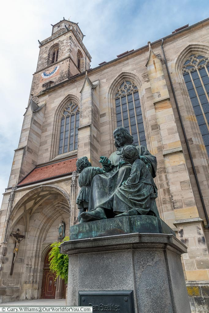 A statue to Christoph von Schmid, a 19th-century writer in front of the bell tower of St George's Minster.