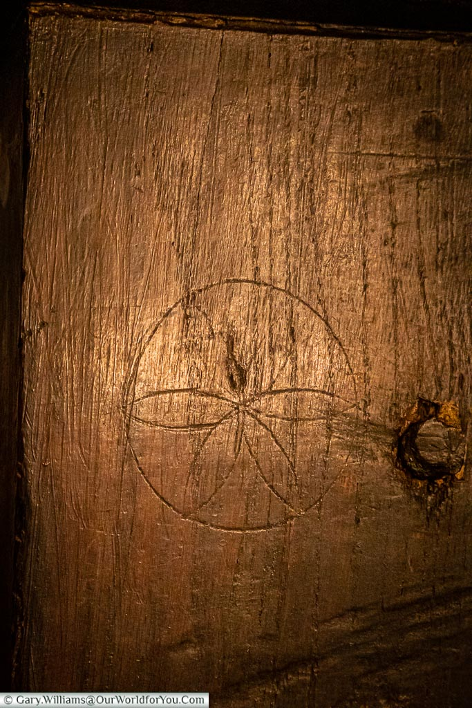 A symmetrical daisy carved into the wooden bannisters at the top of the stairs to ward off evil spirits.