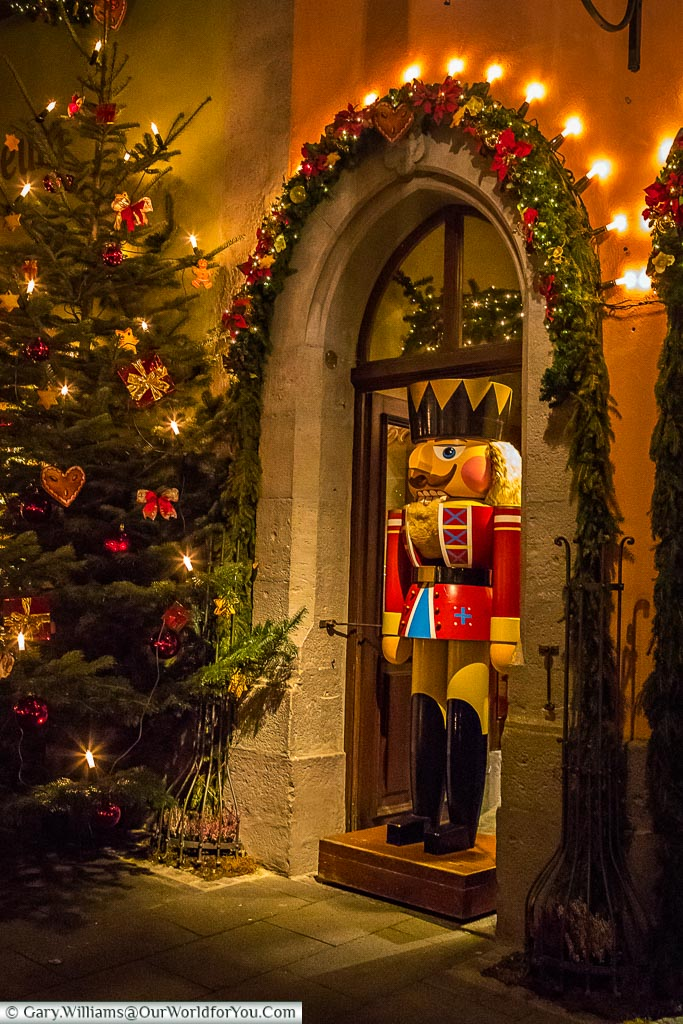 A lifesized soldier nutcracker stands in a decorated doorway of the  Käthe Wohlfahrt store in Rothenburg ob der Tauber, next to a Christmas tree.
