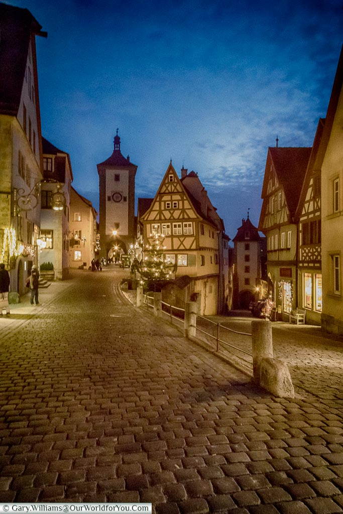 A view of a split in the cobbled lane leading from Rothenburg og der Tauber main town square to one of the gate towers at dusk under a blue sky.