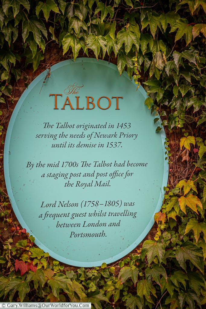 A plaque mounted on the external wall of The Talbot Inn detailing its history through time.