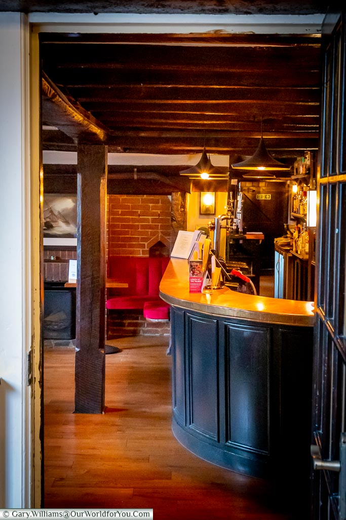 Looking through the dining room door to a view of the traditional copper-topped bar under the open beam ceiling.