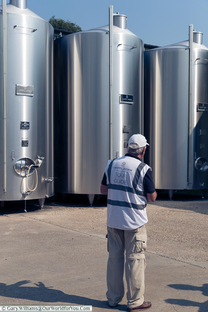 Tony standing in front of the stainless steel vats explaining the process one the wine has been pressed and transferred to these containers.