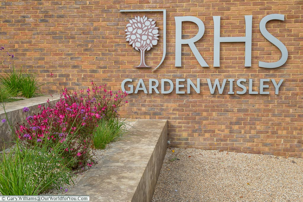 The RHS Garden Wisley sign mounted on a brick wall at the entrance to the gardens.