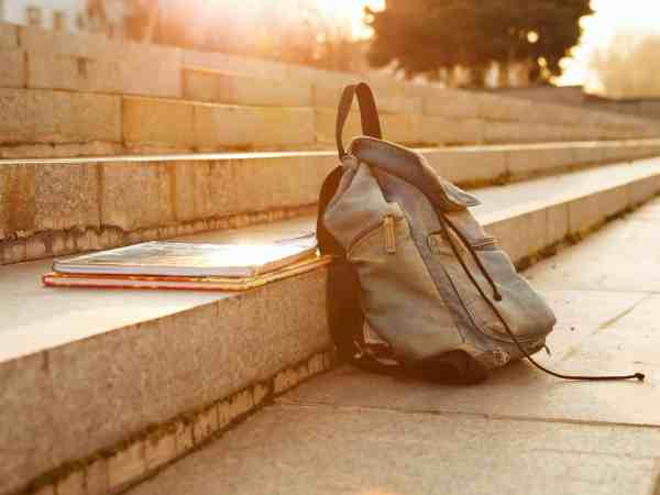 16318616 – old denim school backpack with copybooks left on the stone steps