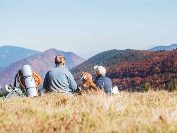Father and son travelers with their beagle dog sit together in mountain valley with beautiful hills view
