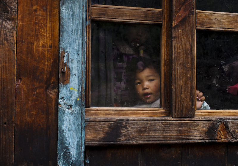 child looking through window in Nepal