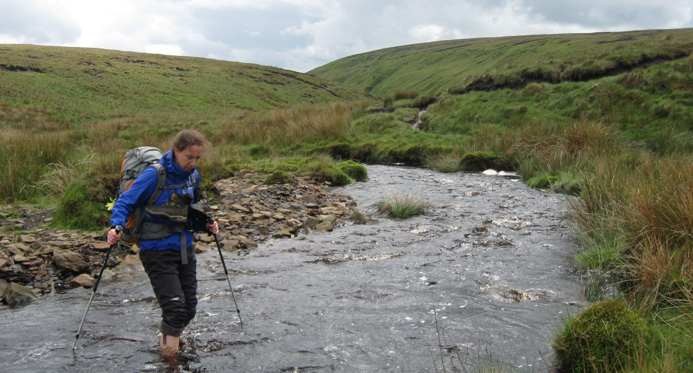 Mika enjoying very wet feet while keep her boots dry in a stream crossing in Dartmoor, England