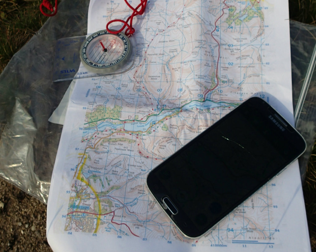 Printed maps in a ziplock, compass and smartphone for on trail navigation
