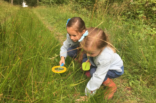 two children looking for mini beasts in grass