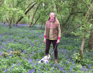 woman with a small dog standing in bluebells in a wood