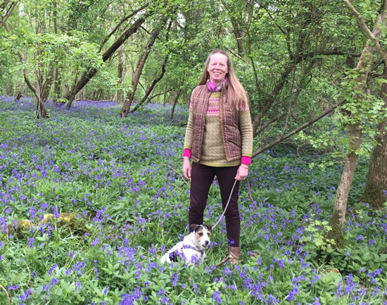 woman standing with dog in bluebells