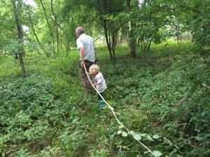 man and boy pulling branch through woodland