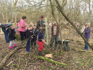 adults and children planting trees in woodland
