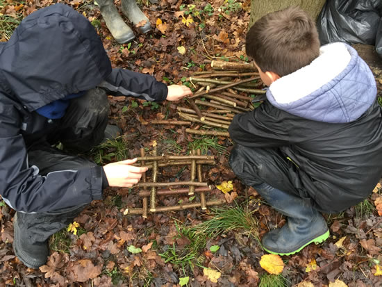 two people building stick tower