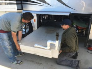Phil Hollingsworth and his son remove fresh water tank to get to the wet bay floor, Lodi CA
