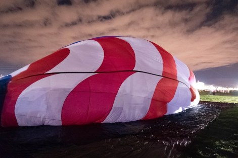 Balloon envelope rests on a tarp as it is being inflated