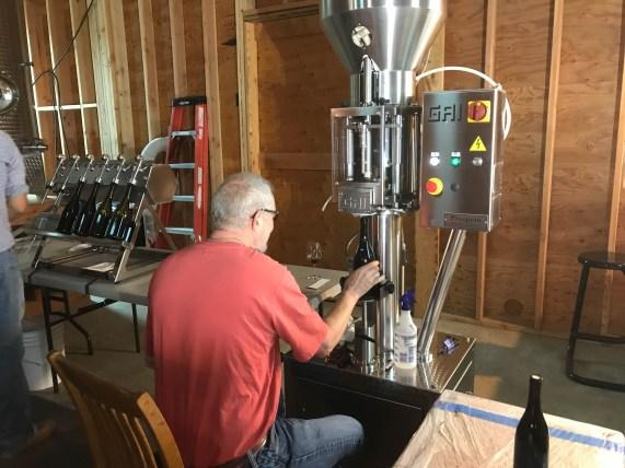 Bruce corking filled bottles at Styring Vineyards