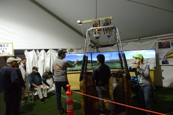 Guests fly a simulator in a tent on the field
