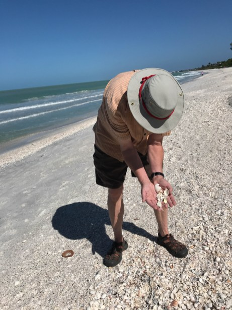 Bruce picsk up handfuls of shells and filters them through his hands to find the keepers
