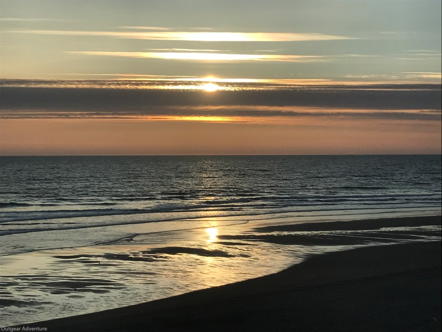 The sun moves through a band of clouds at Ocean Shores